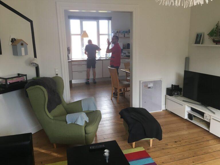 Stue åbent mud til køkken, hvor der står to beboere